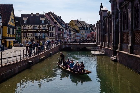 Colmar, France - April 27, 2017 : People riding boat on a river by Petit Venice regions of Colmar on a sunny day. 新聞圖片
