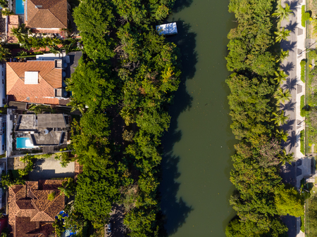 Aerial view o Marapendi canal in Barra da tijuca on a summer day. Green vegetation can be seen on both sides, as well as houses