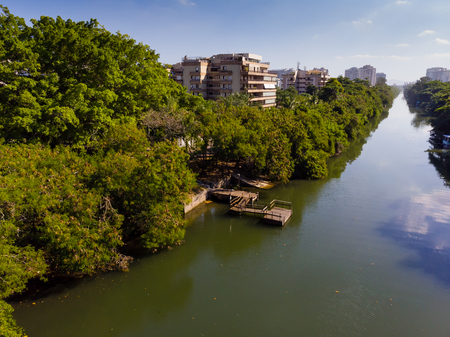 Aerial view o Marapendi canal in Barra da tijuca on a summer day. Green vegetation can be seen on both sides, as well as houses.