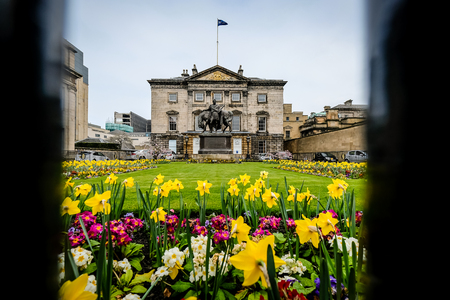 Edinburgh, Scotland - April 27, 2017: Headquarters of the Royal bank of scotland seen through the fence, with flower garden in the foreground on a cloudy day