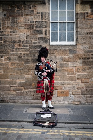 Edinburgh, Scotland - April 27, 2017: Bagpipe player with traditional scottish highlander robes playing on the Royal Mile 新聞圖片