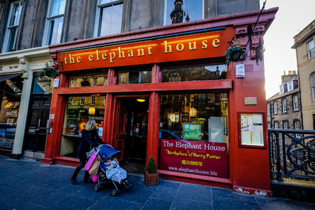EDINBURGH, SCOTLAND - April 2018: Woman with trolley walks by The Elephant house cafe, made famous as the place of inspiration to writer J.K. Rowling, author of Harry Potter.
