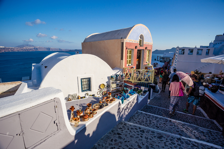 Santorini, Greece - May 5, 2014 : Typical street in Santorini with arts and crafts beind sold on a store and tourists walking with cameras and bags. Gorgeous view of the ocean and cliffs on the side.