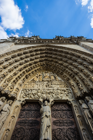 Wide angle photo of entrace gates of the Notre Dame Cathedral in Paris, France.