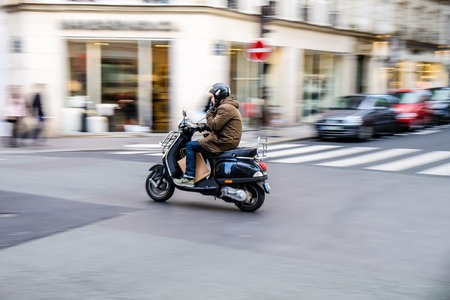Paris, France - May 2, 2014 : Man comutes throught Paris with scooter while smoking, motion blur effect shows only rider in focus 新聞圖片