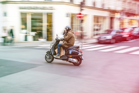 Paris, France - May 2, 2014 : Man comutes throught Paris with scooter while smoking, motion blur effect shows only rider in focus Editorial