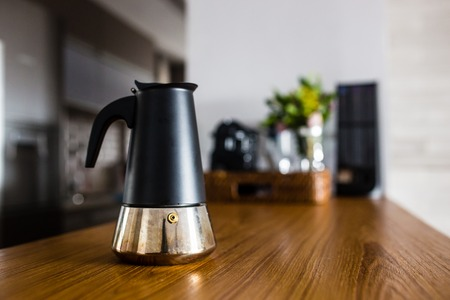 cup of fresh espresso coffee on wooden kitchen counter with interesting perspective, with cup in focus and blurred background.