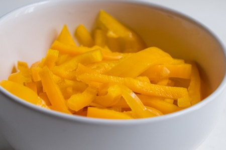 top view of sliced yellow bell pepper on white counter top.