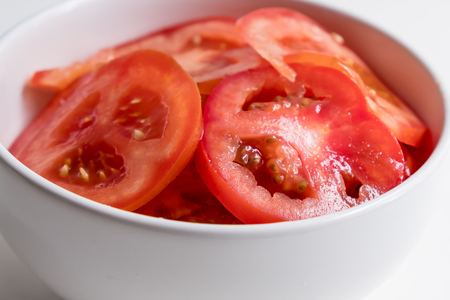 top view of sliced tomatoes in white bowl on white counter top.