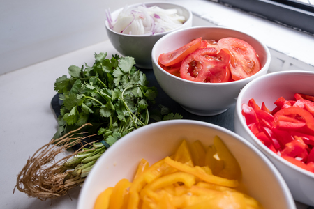 four cups of sliced vegetables on white counter top: onions, red peppers, tomatoes and yellow peppers.