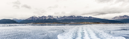 Panorama of mountain view from lake, boat waves can be seen, ushuaia, Patagonia, argentina