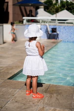 Little girl in white summer dress, white hat and orange slippers looking at pool during a sunny day in summer