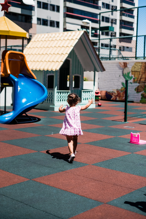 little toddler girl in pink dress running around playground, with her back to the camera, during a summer day. Foto de archivo