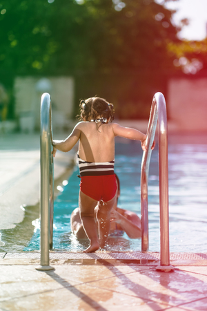 Little girl entering swimming pool via metalic stairs during a sunny day in summer, while mother splashes water on her