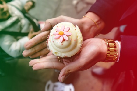woman holding white and pink cupcake in her hands, child in background, colored light leak filter
