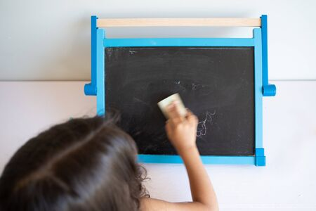 Small girl with long brown hair erasing small blackboard with white surroundings seen from behind