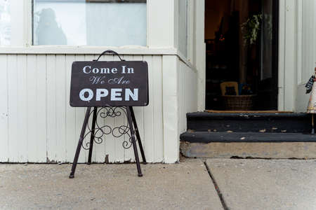 Retail and shopping image of an open sign in a store front. Sign read come in we are open .