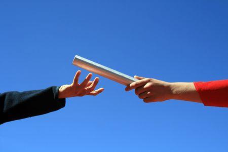 relevos: manos pasa el batton contra el cielo azul  Foto de archivo