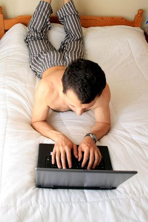 man on working on laptop in bed photo