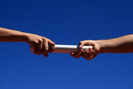 hands passing the batton against blue sky Stock Photo - 3069091