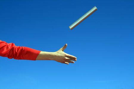 hands passing the batton against blue sky photo