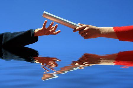 handen passeren van de batton tegen blauwe hemel