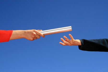 hands passing the batton against blue sky Stock Photo - 3982991