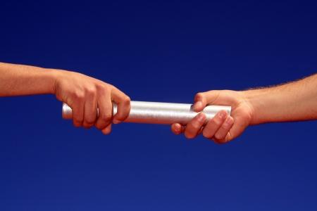 relevos: manos que pasa por el batton contra el cielo azul