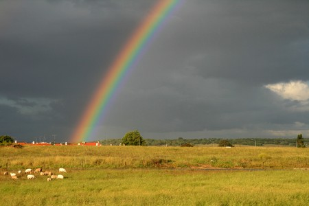 sunny and rainy sky with rainbow Stock Photo