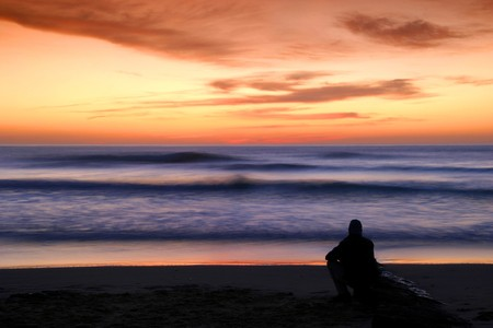 morning glory: man alone watching sunset in the beach