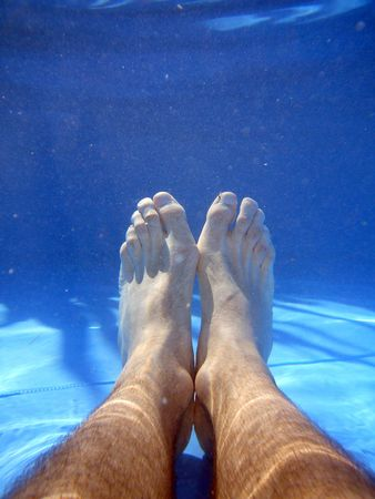 underwater picture of legs on the swimming pool photo