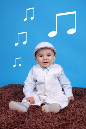 Portrait of a happy baby boy Isolated on blue background listen to musical notes Stock Photo - 10601263