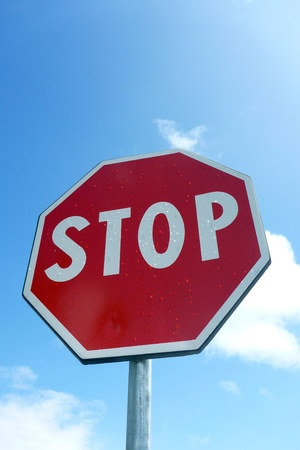 Stop sign against blue cloudy sky