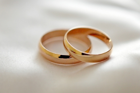 marriage ceremony: Two wedding rings with white flower in the background, wedding photo Stock Photo