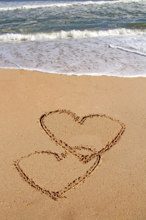 evoke: handwritten heart on sand with wave approaching Stock Photo