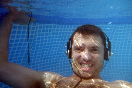 man underwater listen music with head-phones Stock Photo