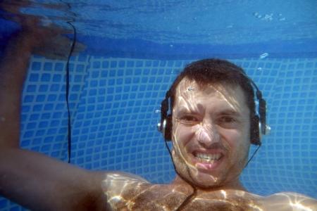 man underwater listen music with head-phones Stock Photo