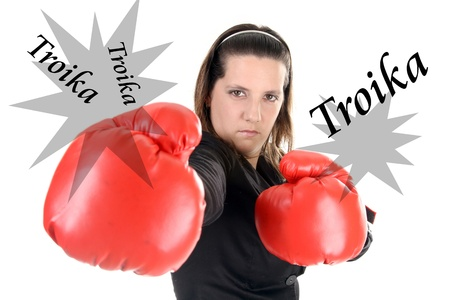 Portrait of a young businesswoman wearing boxing gloves photo