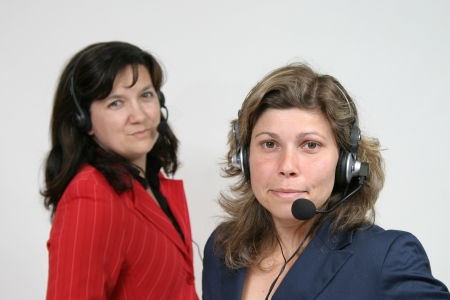 Young friendly brunette woman with headset smiling during conversation photo