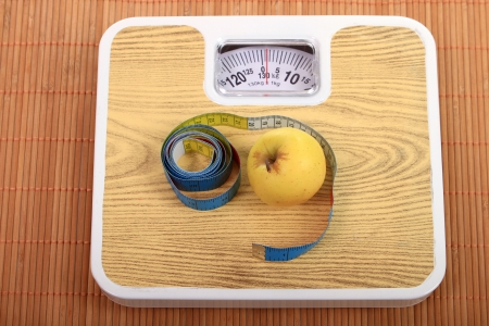 yellow apple and measure tape above the balance