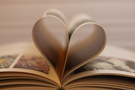 book pages open heart-shaped, with its shadows