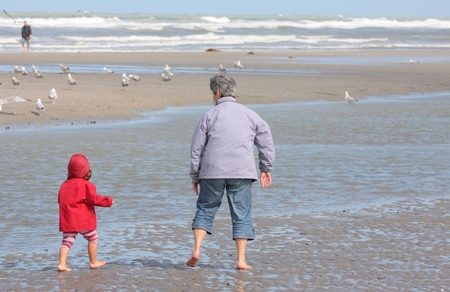Grandmother and granddaughter walking on the beach with feet in water