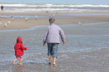 grandchild: Grandmother and granddaughter walking on the beach with feet in water Editorial