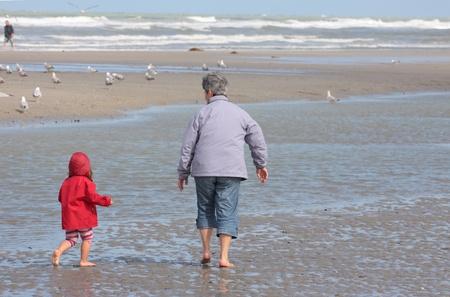 Grootmoeder en kleindochter wandelen op het strand met voeten in het water