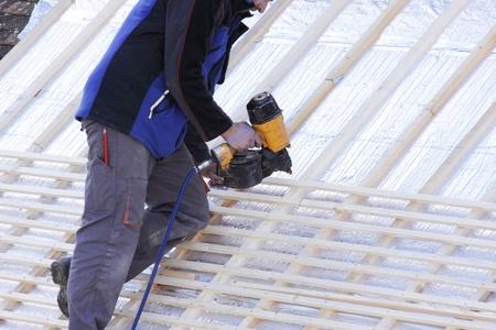 dakdekker werkt aan een nieuw dak in hout