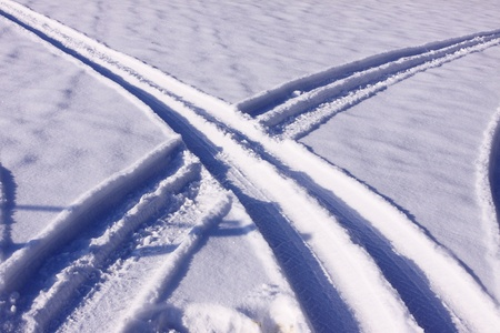 sidelit: tire tracks in the snow in winter