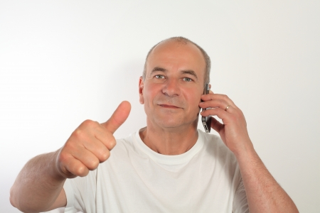 Happy senior man while talking on a mobile cell phone  photo