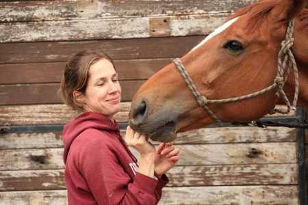 Beautiful women give an apple to her horse photo