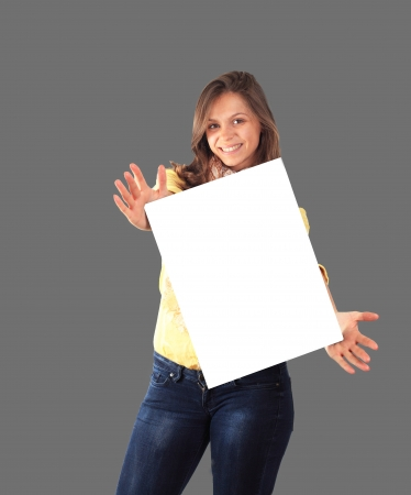 Portrait of a happy young woman holding a blank billboard over grey background photo