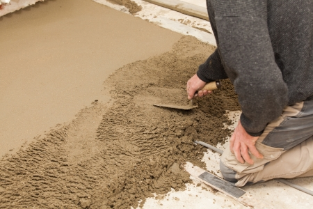 leveling: mason leveling the cement screed Stock Photo